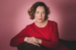 Hier zie je actrice Lot Bobbink in haar rode jurk op een sofa zitten met haar armen over elkaar. De roze achtergrond past goed bij haar rode jurk. Lot heeft haar casting portfolio laten uitbreiden door bekende Nederlandse fotograaf Nikki Hoff. Nikki is de beste castingfotograaf in Zuid Holland.