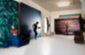 De fotostudio beschikt over verschillende settings. Je ziet in deze studio dat er een jungle achtergrond is, een egale blauwe achtergrond, een witte achtergrond en een houten achtergrond. Deze interieurfoto van de studio geeft mooi weer wat de mogelijkheden zijn binnen de fotostudio. Dit is Studio86 in Alphen aan den Rijn.