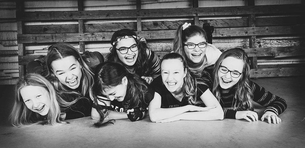 Zwart/wit foto van een kinderpartijtje, gemaakt bij Studio86. De tofste fotostudio in Zuid Holland!  Black and white photo of laughing young girls. Photoshoot of a kids birthday party.