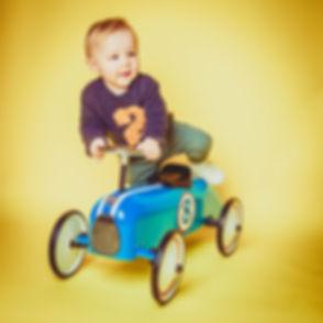 Studiofotografie voor kinderen. Deze kleuter is tegen een gele achtergrond gefotografeerd. Hij stapt net op zijn retro roller.  Studio photography for kids. This toddler is photographed against a yellow background.