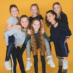Deze jonge meiden zijn tussen de 8 en 10 jaar en de jarige is 10 jaar geworden! Deze fotoshoot was ter ere van haar verjaardag waarbij we vrolijke achtergronden hebben gebruikt zoals deze gele.  Friends sitting on each others back for a photoshoot during a children's birthday party.
