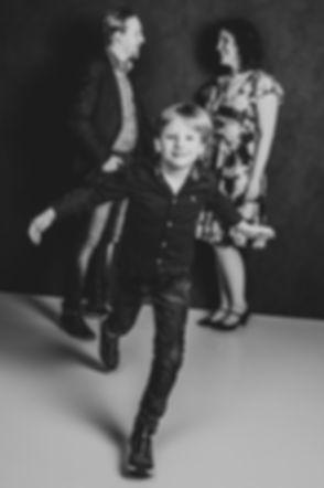 Op deze professionele zwart wit portretfoto zie jij papa en mama die elkaar verliefd aankijken terwijl hun zoon richting de camera komt rennen. Tijdens een gezinsfotoshoot bij Studio86 kan jij uitgaan van een spontane en creatieve fotoshoot. De prijslijst van een fotoshoot kun je opvragen.
