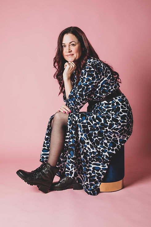 Wil jij een glamour fotoshoot boeken in Zuid Holland? Dan is Studio86 de meest bekende fotostudio in deze regio. Je kan bij Nikki een professionele fotoshoot boeken. Op deze glamourfoto zie je een dame zitten in een lange jurk op een fluweel blauw krukje op een roze papieren achtergrond.