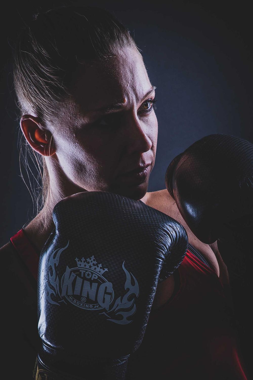 Stoere vrouw doet aan kickboxen. Deze sportieve dame heeft kickbox handschoenen aan en is klaar voor gevecht. Deze foto heeft een extra stoere tint doordat er gebruik is gemaakt van flitslampen.