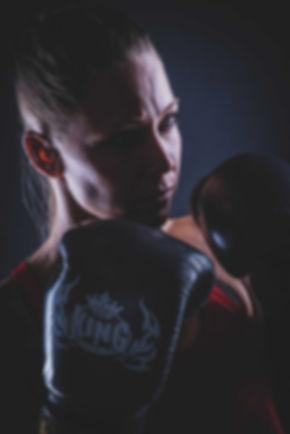 Een close up van een stoere dame die aan kickboksen doet. Door de zwarte achtergrond en het lichtgebruik word deze foto extra stoer gemaakt. Deze professionele portretfoto is gemaakt tijdens een fitness fotoshoot.  Close up of a young lady doing kick boxing. Black background, boxing gloves on a girl.