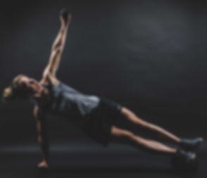 Deze fitness oefening vereist kracht en balans en leent zich goed voor een fitnessfoto! Deze fitgirl is gefotografeerd tijdens een fitness fotoshoot.  Fitness pose in the photostudio on a black background. Sportive woman.