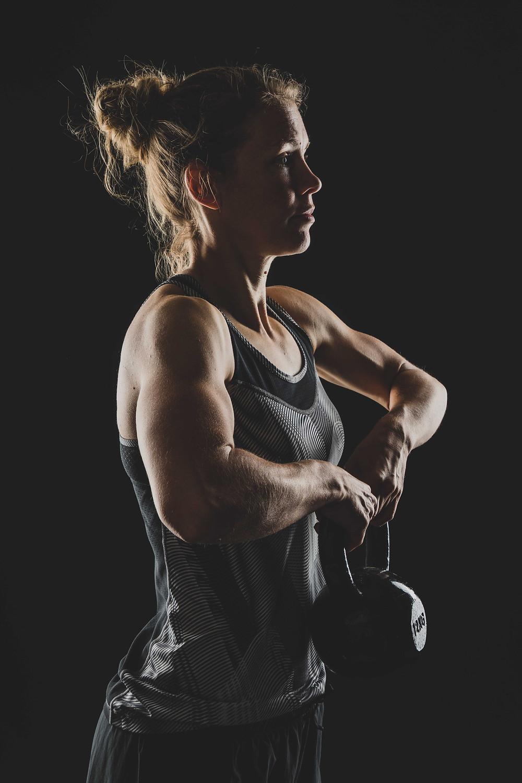 Sportieve dame met kettlebell. Deze sportfoto is gemaakt tijdens een fitness fotoshoot waarbij sportieve foto's van jou worden gemaakt terwijl jij jouw sport uitoefent.