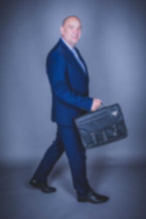 Een buschauffeur die met zijn tas aan het lopen is. Een grappige foto die is gemaakt tijdens een zakelijke fotoshoot. Deze ondernemer is zzper en verhuurd zichzelf als buschauffeur. Hij heeft deze professionele profielfoto laten maken bij de bekendste fotostudio van Nederland. Bus driver holding he's bag. Professional photo made by a famous photographer.