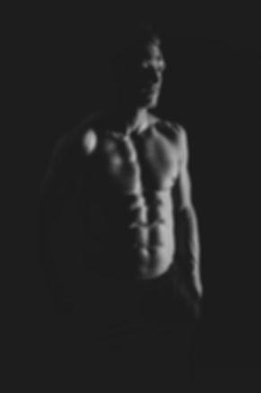 Fitness fotoshoot bij Studio86. Door het gebruik van een zwarte achtergrond en een goede belichting worden de spieren van het droog getrainde lichaam nog beter zichtbaar.  Black and white sport photography. Here u see a sexy man with abs.