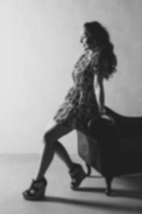Zwart/ wit totaal foto van een jonge vrouw die mooi poseert op een bank. Gemaakt met 1 flitslamp in de fotostudio van bekende fotograaf Nikki Hoff. Black and white full body shot of a young woman who's posing on a couch. Photograph is made with one flash light in the photo studio of famous photographer Nikki.