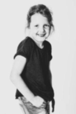Wil jij ook toffe portretfoto's van jouw dochter laten maken? Nikki is gespecialiseerd in kinderfotografie en helpt jou hier graag bij. Ze heeft een ruime fotostudio in Zuid Holland en de studio beschikt over vele verschillende achtergronden.  Black and white portrait photo of a young girl.