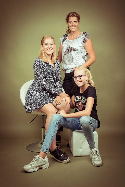 Trotse moeder met haar 2 dochters. Een mooie gezinsfotoshoot van moeder en dochters. Statische portretfoto gemaakt op een olijfgroene achtergrond in een fotostudio. Proud mother of 2 daughters. This family shoot is made in the best photo studio in Holland.