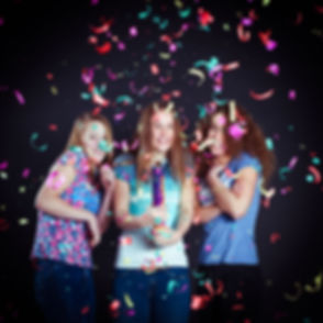Natuurlijk maken we ook gebruik van confetti tijdens een zussen fotoshoot! Op de zwarte achtergrond, komt de confetti mooi naar voren.  3 sisters during a photoshoot in the photo studio using confetti and looking scared.