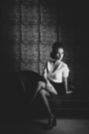 Bij deze portretfoto heeft fotografe Nikki nét de lamp wat aan de zijkant gezet, zodat je net een beetje schuduw krijgt aan 1 kant het het gezicht. Zo voorkom je dat de foto vlak word en creëer je meer diepte. Wil jij ook model worden en je portfolio aanvullen met toffe portretfoto's? Nikki Hoff is de aangewezen fotograaf om jou te helpen!   Black and white photo of a young sexy woman. She is sitting on a chesterfield couch.