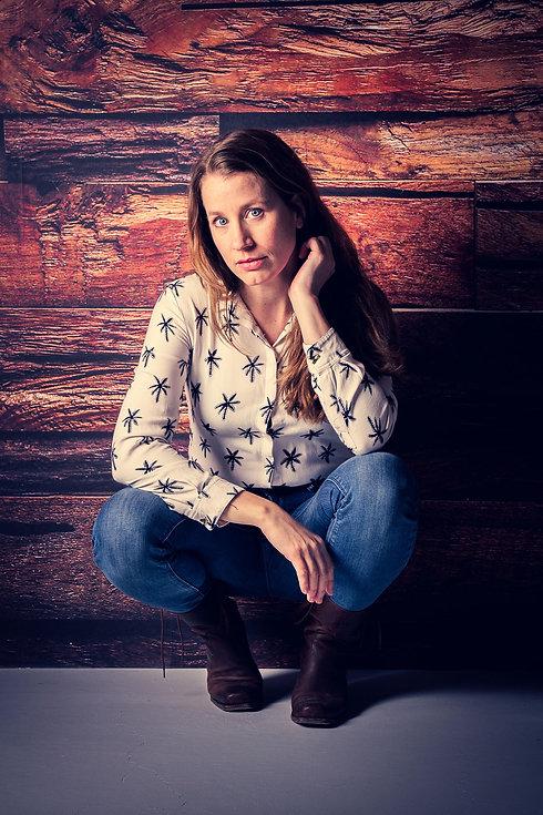 Voor professionele castingfoto's ga je naar bekende fotograaf Nikki Hoff. Zij heeft een moderne fotostudio waar ze een gevarieerde reportage aan castingfoto's kan maken in één fotoshoot. Hier zie je Vivian Dabrowski voor een houten wand op haar hurken zitten.