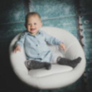 Kijk deze peuter eens stoer op de foto staan. Deze kleine meid is vandaag jarig en is 1 jaar geworden. Dat hebben we gevierd met een gevarieerde en spontane fotoshoot.  Toddler sitting in a white chair. Made during a kids photoshoot.