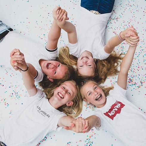 Wil jij ook zo'n vrolijke portretfoto laten maken tijdens een kinderpartijtje? Hier liggen de kinderen op de grond tussen de confetti. Deze creatieve, gezellige, spontane foto van deze tieners is gemaakt door professionele fotografe Nikki Hoff.