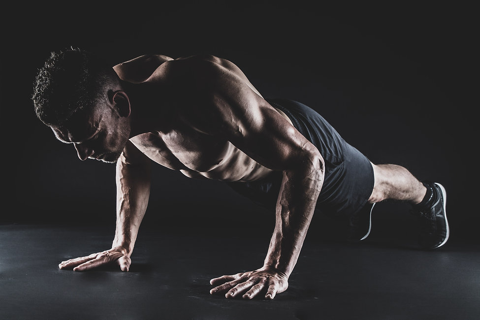 Deze gespierde man doet een push up tijdens een fitness fotoshoot.  This musculair man does a push up during a fitness photoshoot.