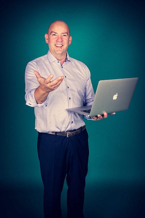 Op deze zakelijke portretfoto zie je een man van middelbare leeftijd staan met een mac laptop in zijn handen. Deze man is leraar en legt wat uit op deze foto. Door de turquoise achtergrond springt hij er goed uit. Deze man is ondernemer en heeft deze foto laten maken voor zijn website en social media. Wil jij ook zo'n professionele profielfoto laten maken? Ga dan naar Studio86. Business picture of a entrepreneur. He's a teacher explaining something to he's students and holds a mac laptop in he's hand.