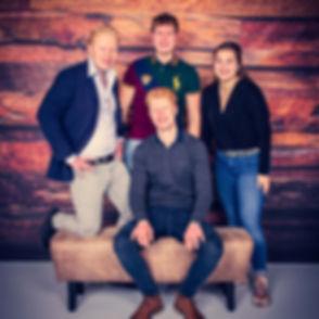Tijdens een familie fotoshoot zal ik ook foto's maken van de kinderen / kleinkinderen samen. Hier zie je drie broers met hun nichtje. Deze professionele portretfoto is gemaakt in de moderne fotostudio van Nikki Hoff. Ze staan hier voor een houten wand. De fotoshoot kan ook op zondag worden geboekt.