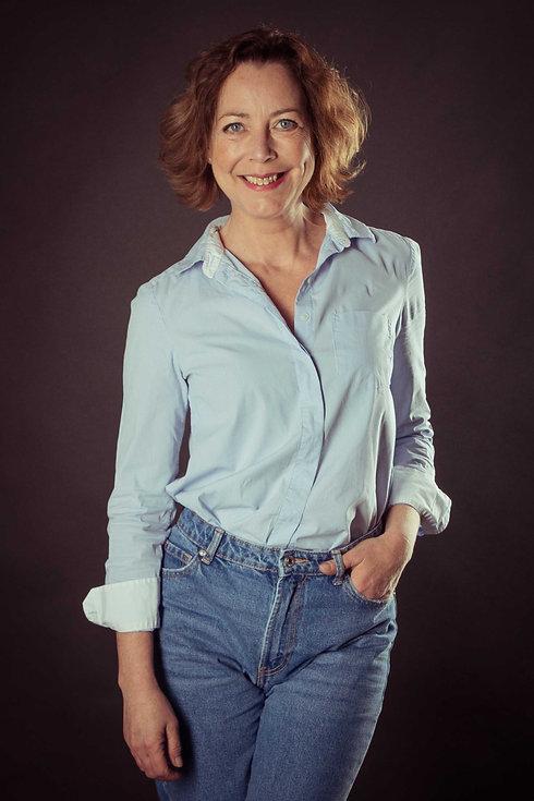Wat is de prijs van een casting fotoshoot? Bij fotostudio Studio86 kost dit €150,- waarbij je 6 digitale foto's ontvangt. Op deze portretfoto zie je actrice Lot Bobbink lachend met haar hand in haar zak en op een zwarte setting.