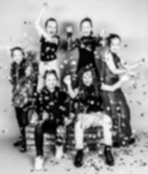 Laat de ballonnen maar knallen! Hier zie je hoe de confetti uit de ballonnen valt over de meiden heen. Een hele gezellige foto die is gemaakt tijdens het kinderpartijtje van een jonge dame die 10 jaar is geworden.  Black and white confetti photography. Children's birthday party.