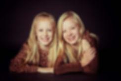 Een lieve close up portretfoto van 2 zusjes die een fotoshoot hebben geboekt bij een kinderfotograaf. Wil jij ook een fotoshoot boeken bij een bekende fotograaf? Ga dan naar de fotostudio van Nikki Hoff voor de mooiste portretfoto's.