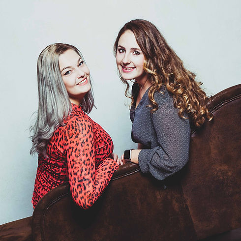 Voor een spontane vriendinnenshoot ga je naar Studio86.  Two friends sitting on a couch looking over their shoulder. Made during a friends photoshoot.