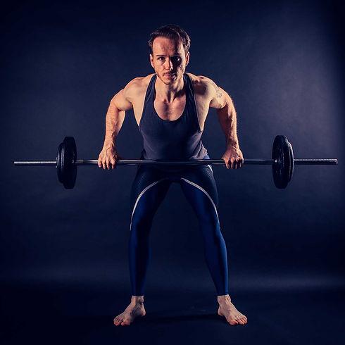 Fitness fotografie is nu ook te boeken bij deze fotostudio. Deze man doet een deadlift met een barbell met gietijzeren gewichten. Ook wel de barbell row genoemd. Voor een sport fotoshoot boek je deze bekende fotostudio. Man doing a deadlift with a barbell.