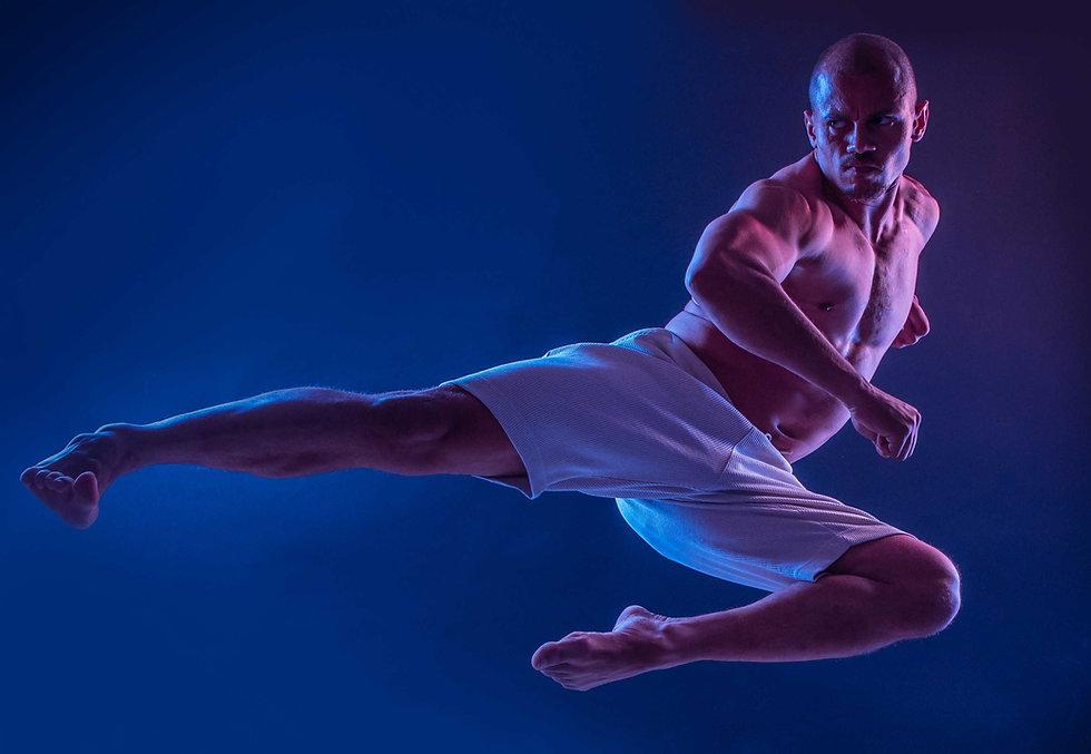 Geoffrey is gespecialiseerd in Marshal Arts en dat hebben we vastgelegd tijdens een sport reportage. Hier zweeft hij als het ware in de lucht.  Sexy muscled guy doing a mashal arts jump. Karate photo made during a sport photoshoot.