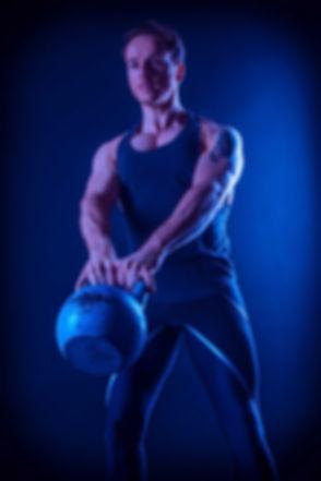 Een fitness instructeur heeft een fitness fotoshoot geboekt bij Studio86. Deze fotostudio maakt de beste fitness foto's. Hij doet hier de kettlebell swing. Voor fitness fotografie kan jij nu bij deze studio boeken! A fitness instructor holds a kettlebell during a fitness photo shoot.