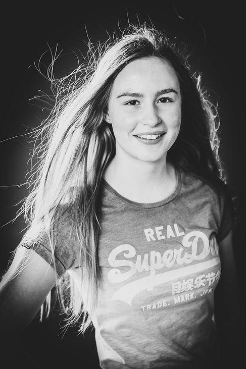 Wil jij doorbreken in de modellenwereld en wil je jouw lookbook vullen met gevarieerde portretfoto's? Bekende fotograaf Nikki Hoff helpt jou hier graag mee. Zij is gespecialiseerd in studiofotografie.  Black and white portrait of a young girl using a wind machine.