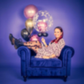 Deze fluweel blauwe chesterfield bank past goed op de paarse achtergrond wat ook weer goed bij de ballonnen past. Deze dame zit in de fauteuil in haar vrolijke jurkje voor een verjaardags fotoshoot. Natuurlijk kan je ook als iemand jarig is deze fotoshoot cadeau geven. In de fotostudio zijn cadeaubonnen aanwezig.