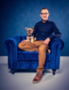 Deze hond met baas foto is gemaakt door bekende dierenfotograaf Nikki Hoff van Studio86. Nikki is gespecialiseerd in hondenfotografie en maakt veel portretten van honden en andere dieren. Hier zit de baas in een blauwe chesterfield stoel met zijn Yorkshire terrier op schoot.