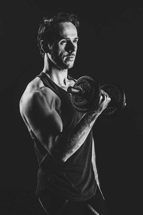 Zwart wit sportfotografie. Deze man heeft een dumbell vast en is zijn biceps aan het trainen. Deze sportfoto is gemaakt in een fotostudio waar je een fitness fotoshoot kunt boeken. Ben jij fitness instructeur zoals deze man of wil jij jouw fitte lichaam op een stoere manier laten fotograferen? Boek dan nu jouw fitness shoot. Man holding a dumbell during a fitness photoshoot.