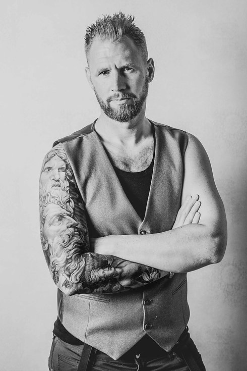 Een zwart wit portretfoto van een stoere man met baard die met zijn armen over elkaar staat. Deze man heeft een sleeve op zijn rechterarm en heeft deze op een professionele manier laten fotograferen door de bekendste fotograaf in Nederland. Black and white portrait photo of a handsome man standing with he's arms crossed. Made by a professional tattoo photographer.