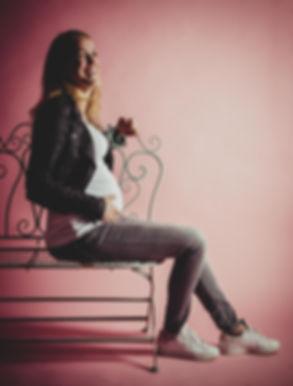 Ben jij in verwachting van een meisje? Dan kunnen we ook een roze achtergrond gebruiken voor deze fotoshoot.  This mommy to be is expecting a baby girl. A happy pregnant woman who is 34 weeks along. She's sitting on a romantic bench on a light pink background.