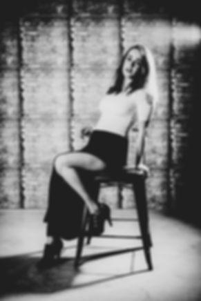 Zwart/wit foto gemaakt tijdens een glamour fotoshoot op de Antonie van Leeuwenhoekweg 36A13 in Alphen aan den Rijn.  Sexy black and white picture of young woman. Here she sits on a high chair in a sexy pose.