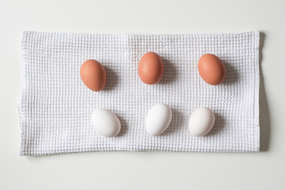 Three brown eggs and three white eggs on a textured kitchen towel