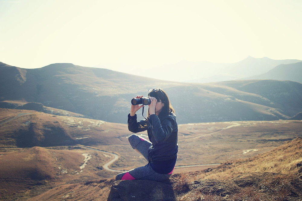 Woman with dark hair and pale skin looking through binoculars in the desert