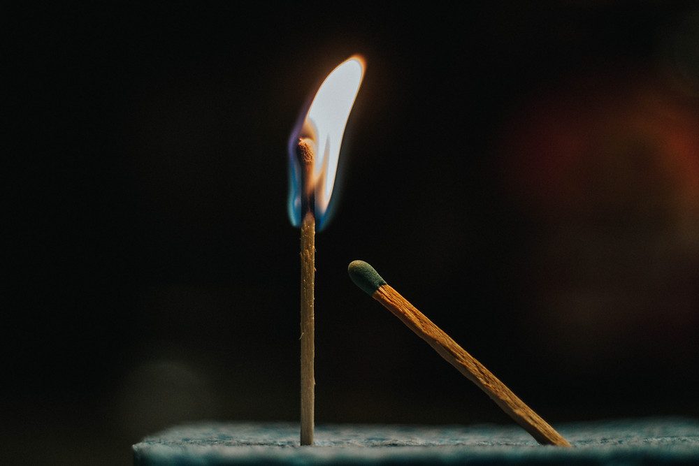 Upright lit match next to unlit match with green tip