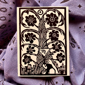 A tarot card with a black-and-white woodcut of a flowering tree