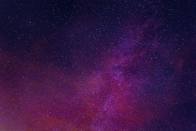 A starry night sky with purple clouds