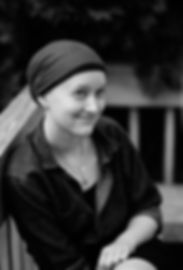 Black-and-white headshot of pale-skinned woman sitting outside, wearing a head scarf and a dark shirt