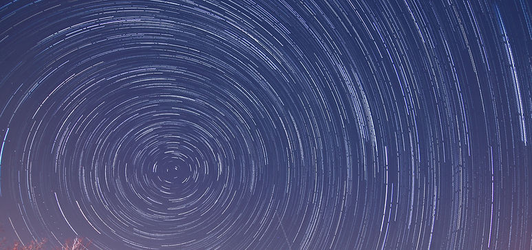 Timelapse photo of star paths creating arcs against a dark blue sky