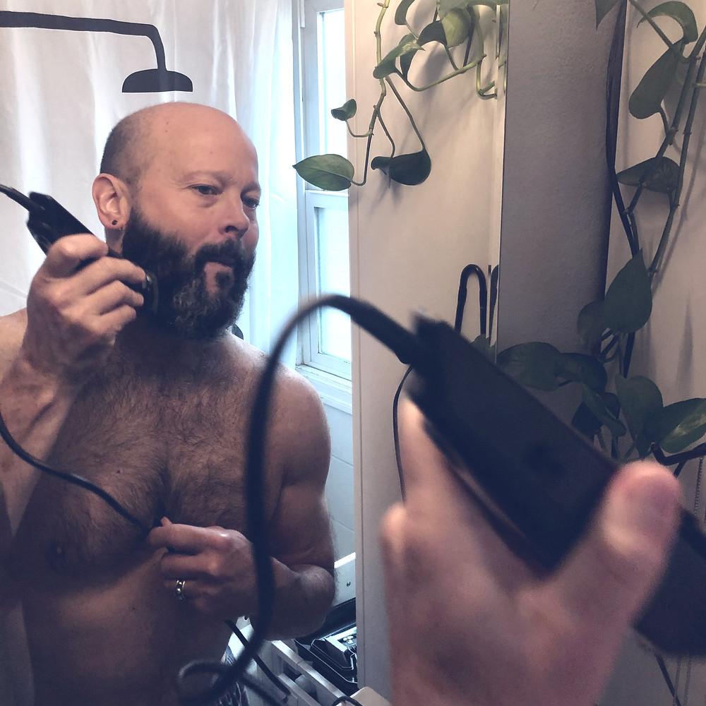 The Original Goddamn Man using an electric trimmer on his beard