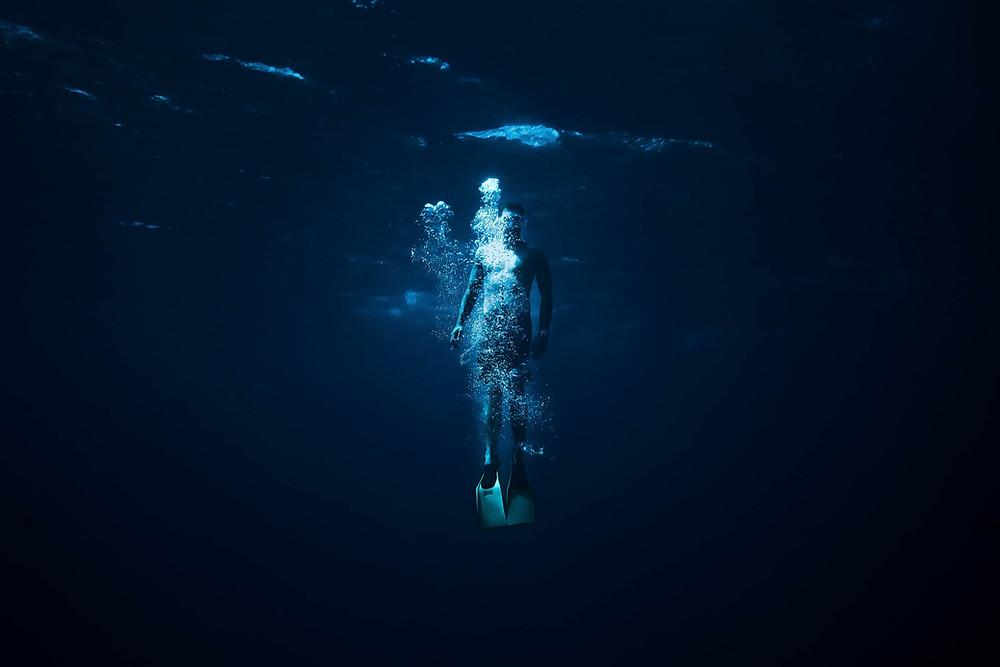 person diving in a dark ocean