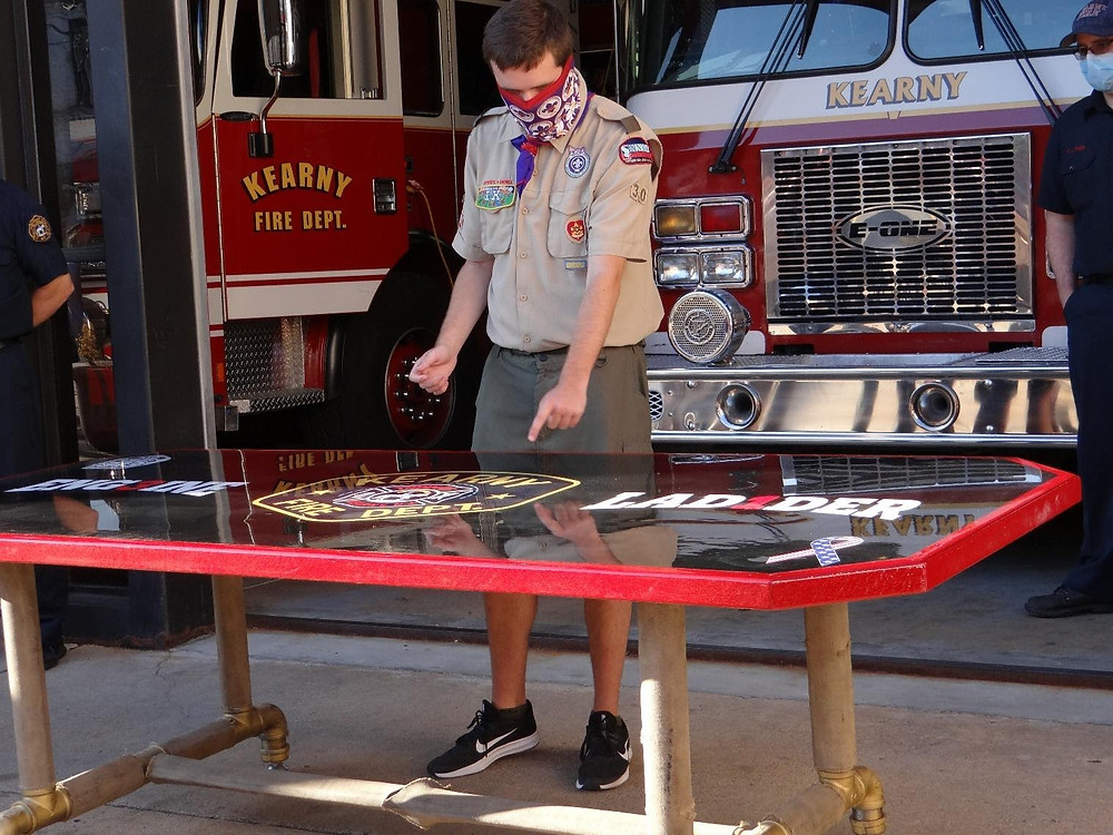 Life Scout John Dec of Troop 305 presents the custom-built table to the firefighters at the Midland Avenue firehouse as the culmination of his Eagle Project to revitalize the dining room