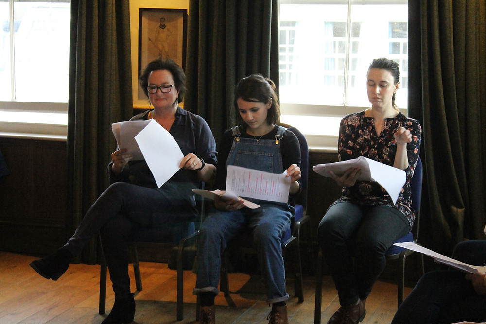 Three actors reading scripts seated in a row