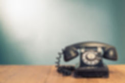 Retro black telephone on wooden table in